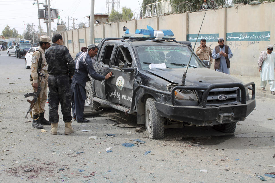 Security personnel inspect the site of a deadly roadside bomb in Helmand province, southern Afghanistan, Sunday, Feb. 21, 2021. Two separate roadside explosions in Afghanistan, Sunday killed and wounded numerous people. (AP Photo/Abdul Khaliq)