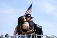 FILE - In this June 15, 2021, file photo, Silvia Guillen, 19, and her boyfriend Joseph Alvarez, 22, both from El Paso, Texas, share a kiss at Universal Studios in Universal City, Calif. COVID-19 deaths in the U.S. have dipped below 300 a day for the first time since the early days of the disaster in March 2020, while the number of Americans fully vaccinated has reached about 150 million. (AP Photo/Ringo H.W. Chiu, File)