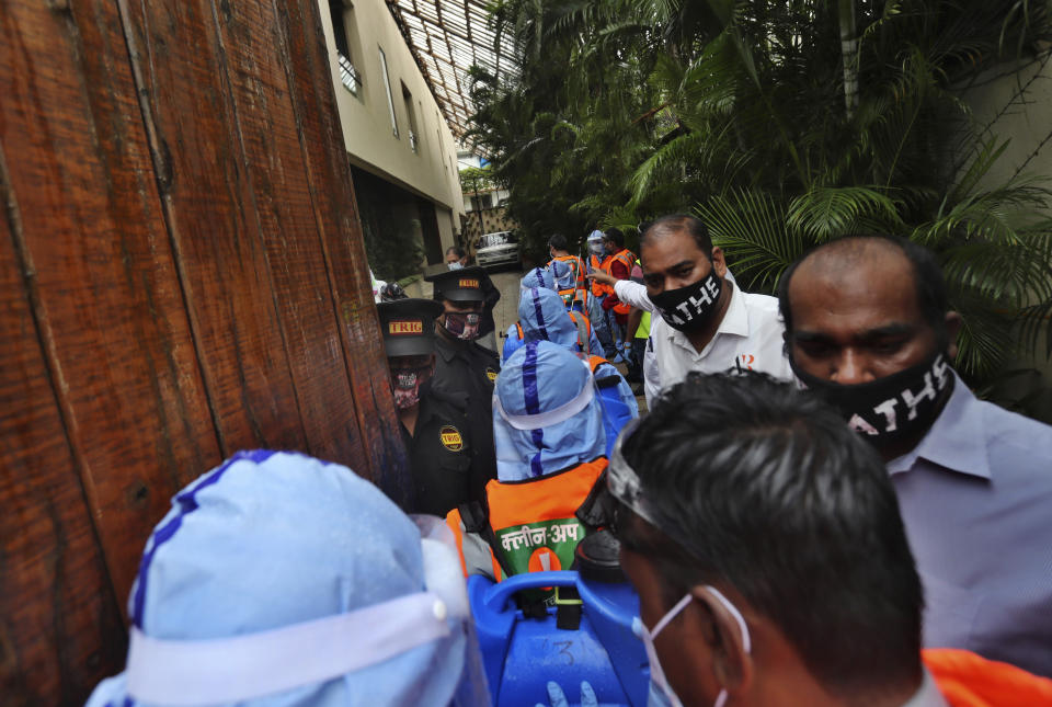Civic workers, in blue, arrive at Bollywood superstar Amitabh Bachchan's residence to sanitize the building after Bachchan and his son tested positive for the coronavirus and were hospitalized in Mumbai, India, Sunday, July 12, 2020. (AP Photo/Rafiq Maqbool)