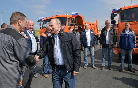 Russian President Vladimir Putin (R, front) greets builders before a ceremony opening a bridge, which was constructed to connect the Russian mainland with the Crimean Peninsula, near the Taman Peninsula in Krasnodar Region, Russia May 15, 2018. Sputnik/Alexei Druzhinin/Kremlin via REUTERS