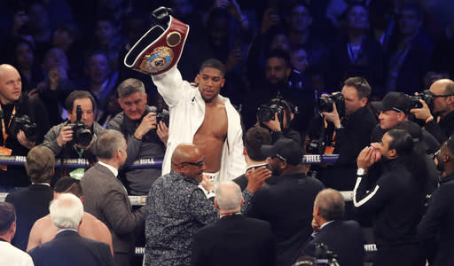 FILE- In this file photo dated Saturday, March 31, 2018, Britain's Anthony Joshua celebrates after his WBA, IBF, WBO and IBO Heavyweight Championship title bout against New Zealand's Joseph Parker in Cardiff, Wales. Joshua was given a 24-hour deadline on Tuesday june 26, 2018, to sign a deal to fight Russian contender Alexander Povetkin or face being stripped of the WBA portion of his world heavyweight boxing titles. (AP Photo/Frank Augstein, FILE)