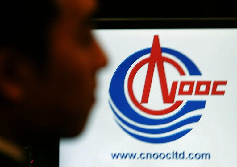 An employee of China National Oil Offshore Company (CNOOC) looks at the company's logo in Hong Kong, on January 23, 2006