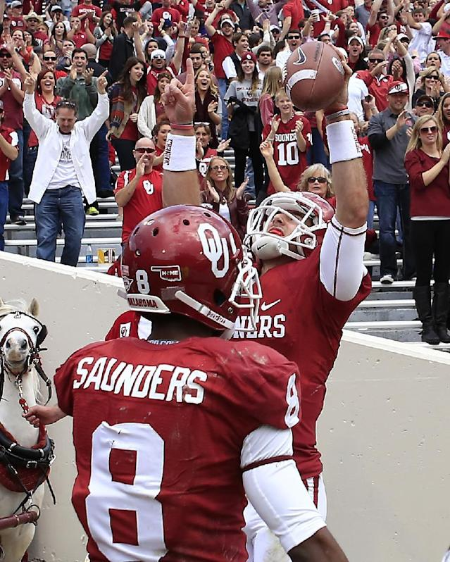 Oklahoma Trevor Knight and Jalen Saunders celebrate after Knight's touchdown against Iowa State in the third quarter of an NCAA college football game in Norman, Okla. on Saturday, Nov. 16, 2013. Oklahoma won 48-10. (AP Photo/Alonzo Adams)