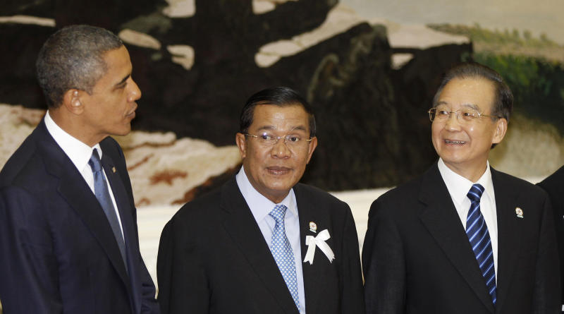 FILE - In this Nov. 20, 2012 file photo, China's Premier Wen Jiabao, right, chats with U.S. President Barack Obama, left, as Cambodia's Prime Minister Hun Sen stands between them during a family photo at the 7th East Asia Summit Plenary Session in Phnom Penh, Cambodia.  China's finding the once friendly ground of Southeast Asia bumpy going, with anger against Chinese claims to disputed islands, once reliable ally Myanmar flirting with democracy and renewed American attention to the region.   (AP Photo/Vincent Thian, File)