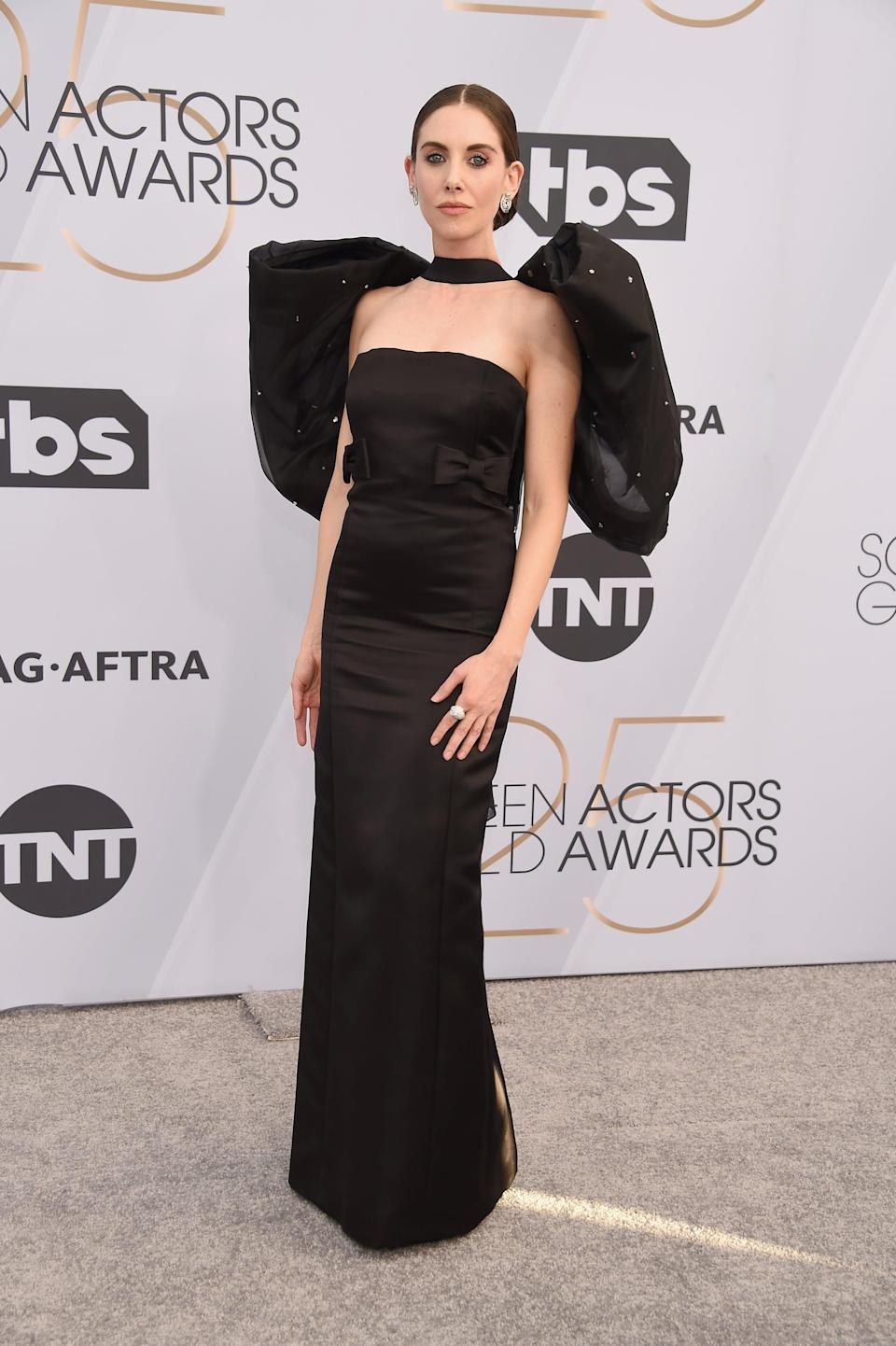 """<p>Wearing <a rel=""""nofollow noopener"""" href=""""https://www.popsugar.com/fashion/Alison-Brie-Black-Dress-SAG-Awards-2019-45724095"""" target=""""_blank"""" data-ylk=""""slk:a black Miu Miu gown"""" class=""""link rapid-noclick-resp"""">a black Miu Miu gown</a> that featured a big bow on the back with Fred Leighton jewels and Jimmy Choo shoes.</p>"""