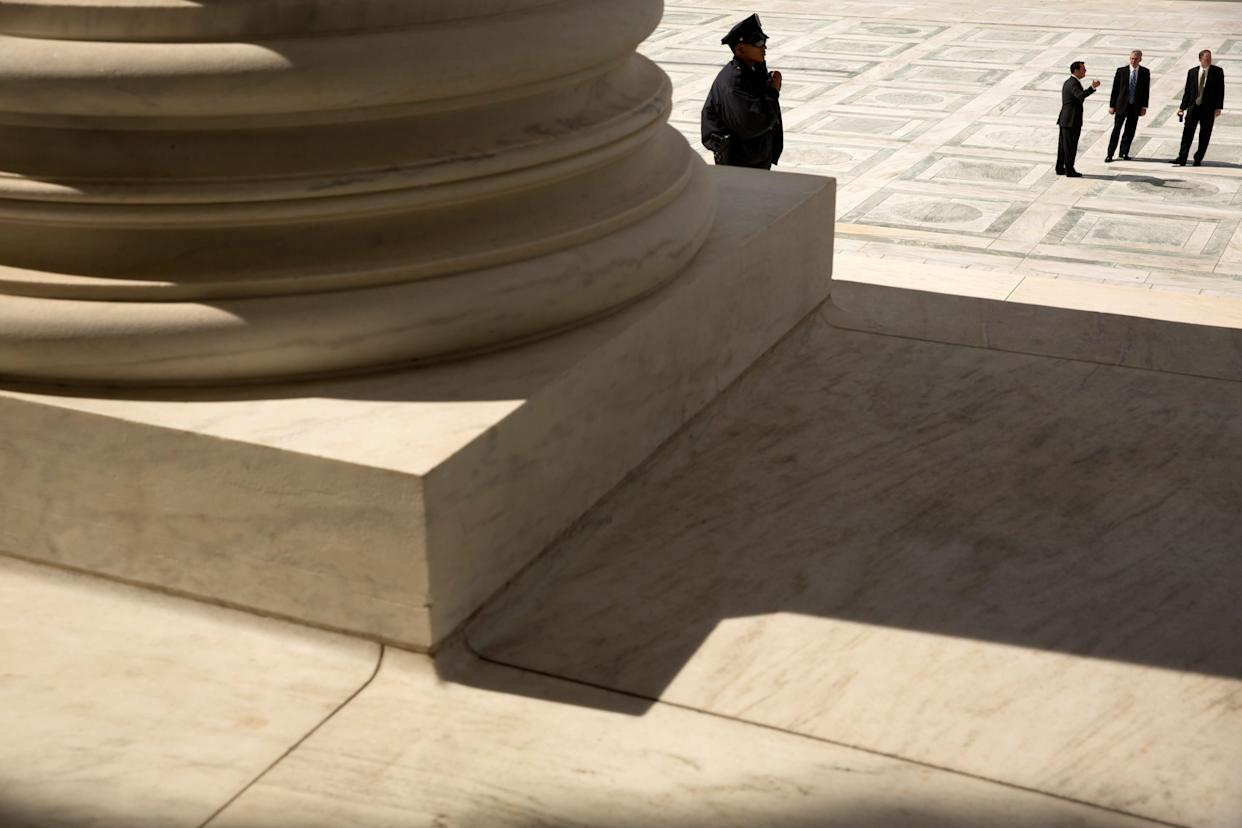 A guard stands on the steps of the U.S. Supreme Court building in Washington on Oct. 5, 2015.