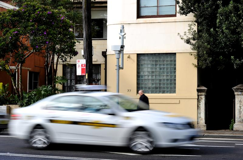 Picture of a taxi speeding past a camera on a suburban street in Sydney