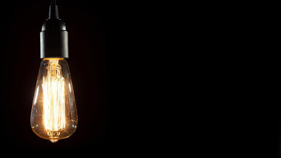 A classic Edison light bulb on black background with space for text.