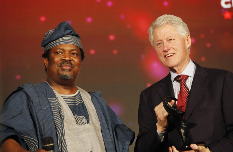 In this photo taken, Tuesday, Feb. 26, 2013, the Chairman of This Day newspaper, Nduka Obaigbena, left and former U.S President Bill Clinton, right, attend the annual This Day awards in Abeokuta, Nigeria. Known more for bringing in celebrities and smiling in photographs next to former Western leaders, a flamboyant Nigerian newspaper publisher now faces a challenge from his most vocal critics _ his own employees. Workers have barricaded the front of This Day newspapers in Lagos, hoping to force publisher Nduka Obaigbena into paying them as much as four months' worth of back salaries due to them. Back pay disputes often hit industries in Nigeria, a country where steady paying jobs remain few, but this crisis has hit a man politically connected to the nation's ruling elite, the second such major business figure to be stung in recent months. (AP Photos/Sunday Alamba)