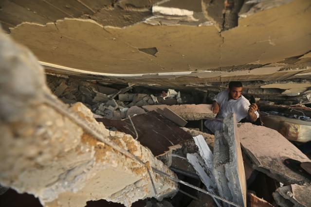 A Palestinian man searches for belongings under the rubble of a house which police said was destroyed in an Israeli air strike in Gaza City July 9, 2014. At least 23 people were killed across Gaza, Palestinian officials said on Wednesday, by a bombardment Israel said may be just the start of a lengthy offensive against Islamist militants whose rockets struck deeper than ever before into Israel. REUTERS/Mohammed Salem (GAZA - Tags: POLITICS CIVIL UNREST TPX IMAGES OF THE DAY)