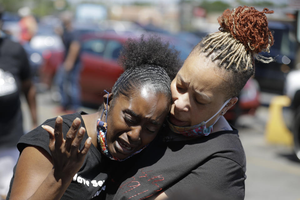 Two women pray, Tuesday, June 2, 2020, in Louisville, Ky., near the intersection where David McAtee was killed Sunday evening. Louisville police say video obtained from security cameras at McAtee's business and an adjoining business show that McAtee fired a gun as police and National Guard soldiers were enforcing a curfew approached his business. (AP Photo/Darron Cummings)