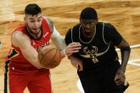 New Orleans Pelicans' Willy Hernangomez and Milwaukee Bucks' Bobby Portis go after a loose ball during the second half of an NBA basketball game Thursday, Feb. 25, 2021, in Milwaukee. (AP Photo/Morry Gash)