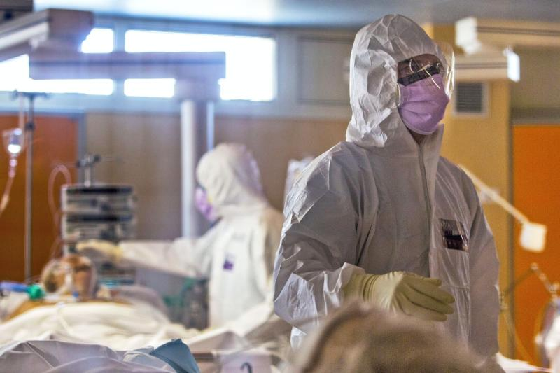 Two health-care workers completely covered by white protective suits and face masks tend to patients on gurneys.