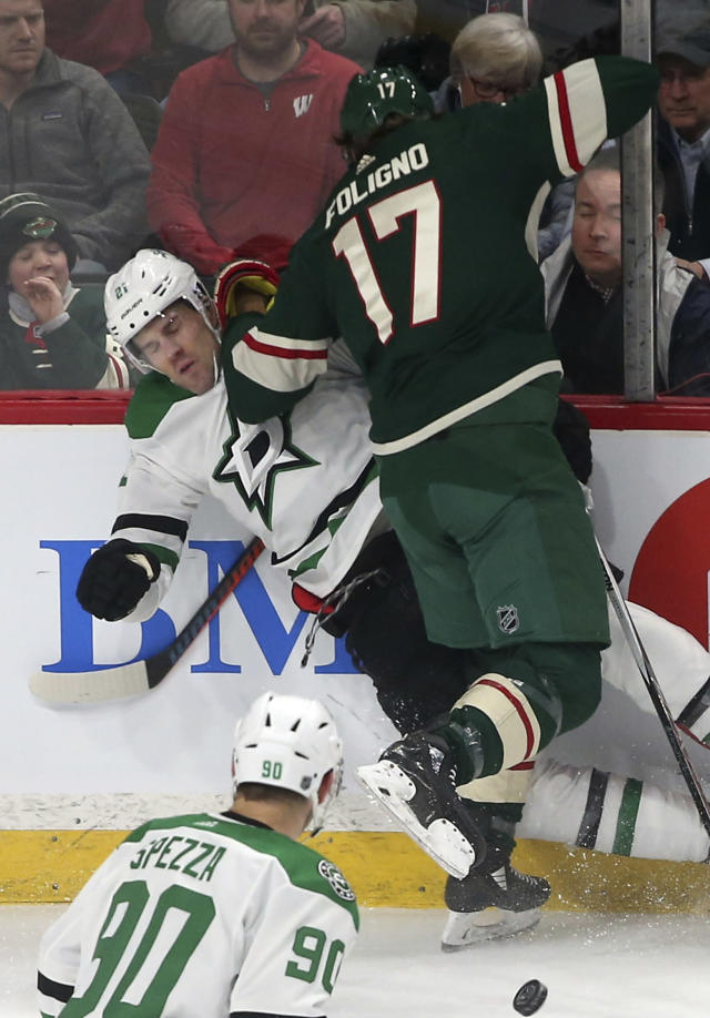 Dallas Stars' Ben Lovejoy, left, is checked into the boards by Minnesota Wild's Marcus Foligno in the first period of an NHL hockey game Thursday, March 14, 2019, in St. Paul, Minn. (AP Photo/Jim Mone)
