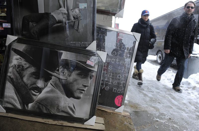 """FILE - This Jan. 22, 2010, file photo, shows festivalgoers walking past a poster of Robert Redford, far left, and Paul Newman in the film """"Butch Cassidy and the Sundance Kid"""" during the Sundance Film Festival in Park City, Utah. A conservative Utah group believes the Sundance Film Festival's lineup featuring 'obscene' movies is at odds with Utah's culture of family values, and wants the state to pull its financial backing. (AP Photo/Chris Pizzello, File)"""