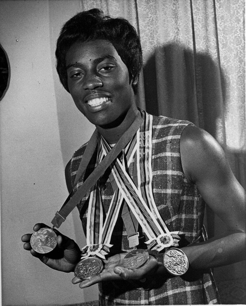 Wyomia Tyus, of Griffin, Ga., displays the three Olympic gold medals and one silver medal she plans to pack away with her track shoes in favor of