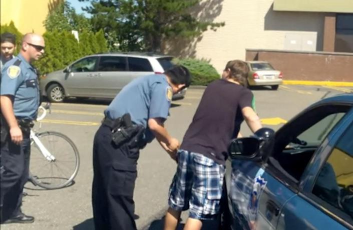 This still image taken from a YouTube video posted by Jake Gillum shows Seattle police arresting a suspect in the theft of Gillum's bike. Gillum's bike was stolen in Portland, Ore., while he was on a date and he was determined to get it back. The quest seemed hopeless, but a week of poring over online postings for his 2009 carbon fiber Fuji paid off when he spotted the road bike offered for sale in Seattle. That sparked an elaborate interstate sting operation last weekend in which Gillum not only got his bicycle back but used it to chase down the suspect before police arrested him. (AP Photo/Jake Gillum)