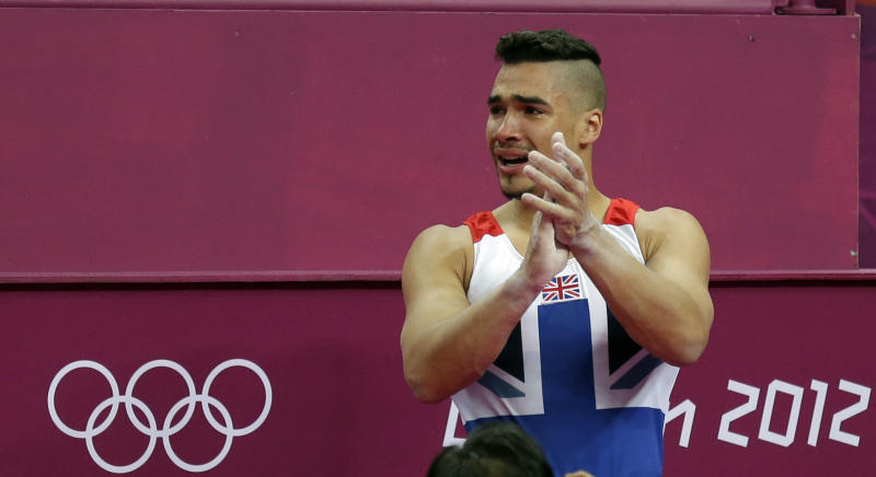 Great Britain's gymnast Louis Smith applauds while crying during the Artistic Gymnastics men's qualification at the 2012 Summer Olympics, Saturday, July 28, 2012, in London. (AP Photo/Gregory Bull)