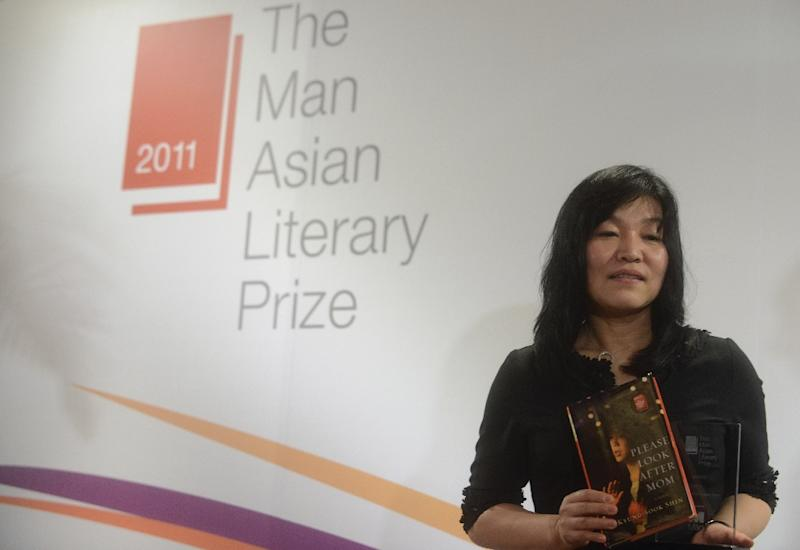 South Korean author Shin Kyung-sook holds her book, Please Look After Mom, and the Man Asian Literary Prize in Hong Kong on March 15, 2012