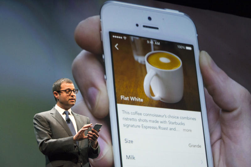 Starbucks Chief Digital Officer Adam Brotman demonstrates how to order a drink using the mobile ordering system during the company's annual shareholder's meeting in Seattle, Washington March 18, 2015. Starbucks Corp will begin offering delivery in New York City and Seattle later this year, when it also plans to expand mobile order and pay services across the United States. REUTERS/David Ryder (UNITED STATES - Tags: BUSINESS)
