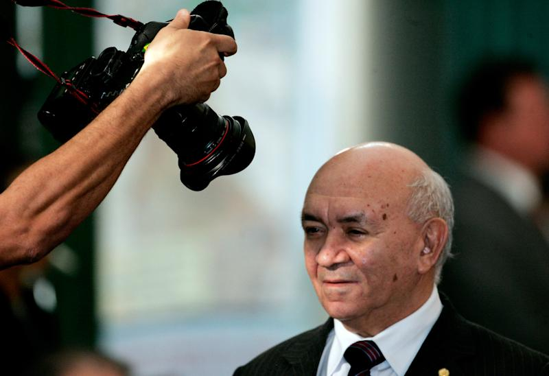 A news photographer takes a picture of former president of the Brazilian Lower House of Congress, Severino Cavalcanti, as he walked to his seat at the start of a ceremony inside Planalto Palace in Brasilia September 29, 2005. REUTERS/Rickey Rogers