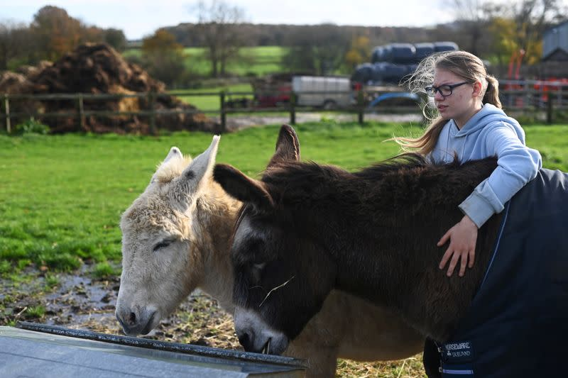 Emily Trice relaxes as she connects with donkeys Milly and Max, during a visit to Future Roots in Sherborne