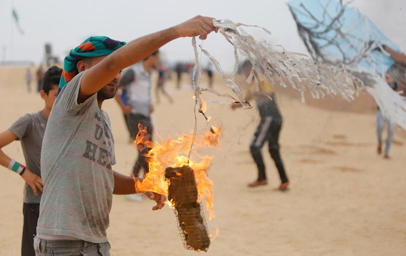 A Palestinians protester attaches an incendiary device to a kite before trying to fly it over the border fence between Gaza and Israel on May 4, 2018