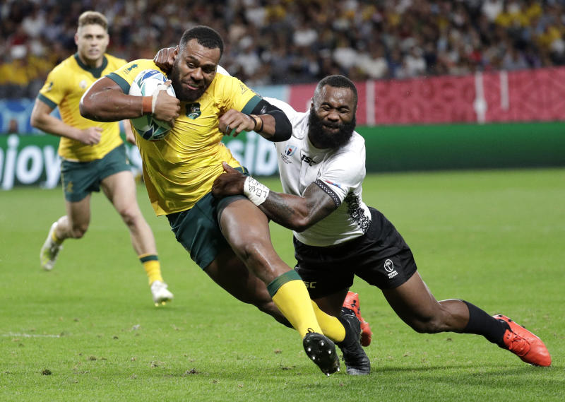 Australia's Samu Kerevi avoids the tackle of Fiji's Semi Radradra to score a try during the Rugby World Cup Pool D game at Sapporo Dome between Australia and Fiji in Sapporo, Japan, Saturday, Sept. 21, 2019. (AP Photo/Aaron Favila)