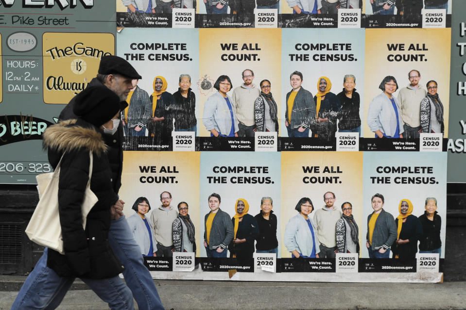 FILE - In this Wednesday, April 1, 2020 file photo,People walk past posters encouraging participation in the 2020 Census in Seattle's Capitol Hill neighborhood. A top lawmaker says the Trump administration is seeking to delay deadlines for the 2020 census because of the coronavirus outbreak. U.S. Rep. Carolyn Maloney said Monday, April 13, 2020 that administration officials also were asking that the timetable for releasing apportionment and redistricting data used to draw congressional and legislative districts be pushed back.(AP Photo/Ted S. Warren, File)