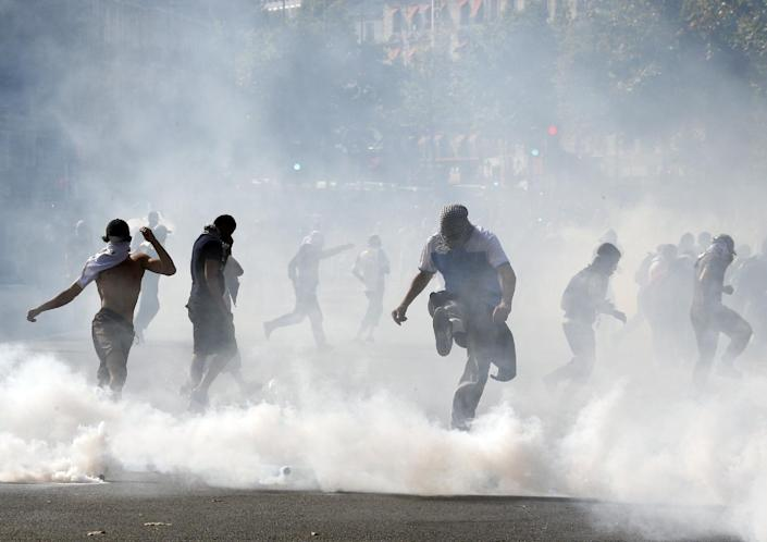 Demonstrators kick tear gas canisters as they clash with riot police in Paris on July 26, 2014 after a protest against Israel's military action in Gaza (AFP Photo/Francois Guillot)