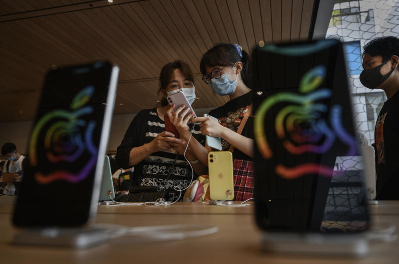 BEIJING, CHINA - JULY 17: Chinese customers look at iphones at the official opening of the new Apple Store in the Sanlitun shopping area on July 17, 2020 in Beijing, China. The new store replaces Apple's first ever China store which opened in 2008 prior to the Beijing Olympics adjacent to the new location. Chinas economy returned to growth in the second quarter of 2020, after historic declines in the first quarter due to the coronavirus pandemic. According to figures released by the government Thursday, the gross domestic product grew 3.2% in the quarter from a year ago, reversing a 6.8% contraction in the first part of the year as the country battled the outbreak. (Photo by Kevin Frayer/Getty Images)