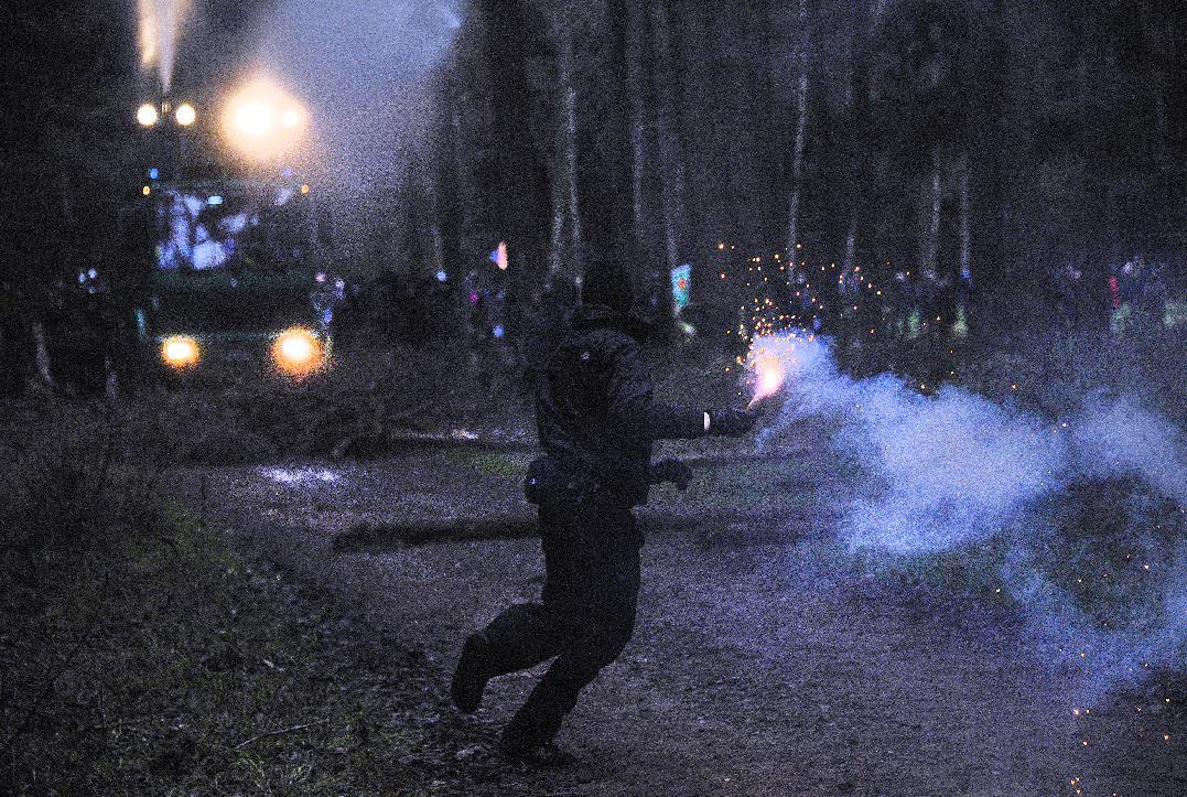 A masked environment activist throw fireworks during clashes with police near Metzingen, A shipment of nuclear waste reprocessed in France crossed into Germany Friday on its way to a controversial storage site that protesters say is unsafe. The train carrying the annual shipment entered western Germany in the morning after delays in France, where activists damaged railtracks in an attempt to halt the cargo. It is the first such shipment from France to Germany since Berlin decided to shut all its nuclear plants by 2022, following the disaster at Japan's Fukushima plant. The transport is due to arrive at the storage site on Sunday. (AP Photo/dapd Sascha Schuermann) (AP Photo/dapd/ Sascha Schuermann)