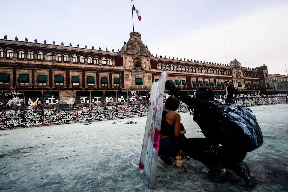 Women take cover as they clash with the police, behind a fence in front of the National Palace, as they protest during a demonstration to commemorate the International Women's Day  in Mexico City, on March 8, 2021. (Photo by PEDRO PARDO / AFP) (Photo by PEDRO PARDO/AFP via Getty Images)