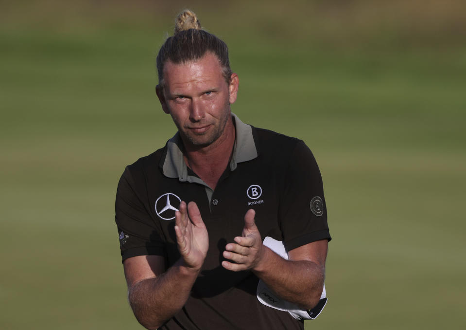 Germany's Marcel Siem acknowledges the crowd after a birdie on the 18th green 18th green during the third round of the British Open Golf Championship at Royal St George's golf course Sandwich, England, Saturday, July 17, 2021. (AP Photo/Ian Walton)