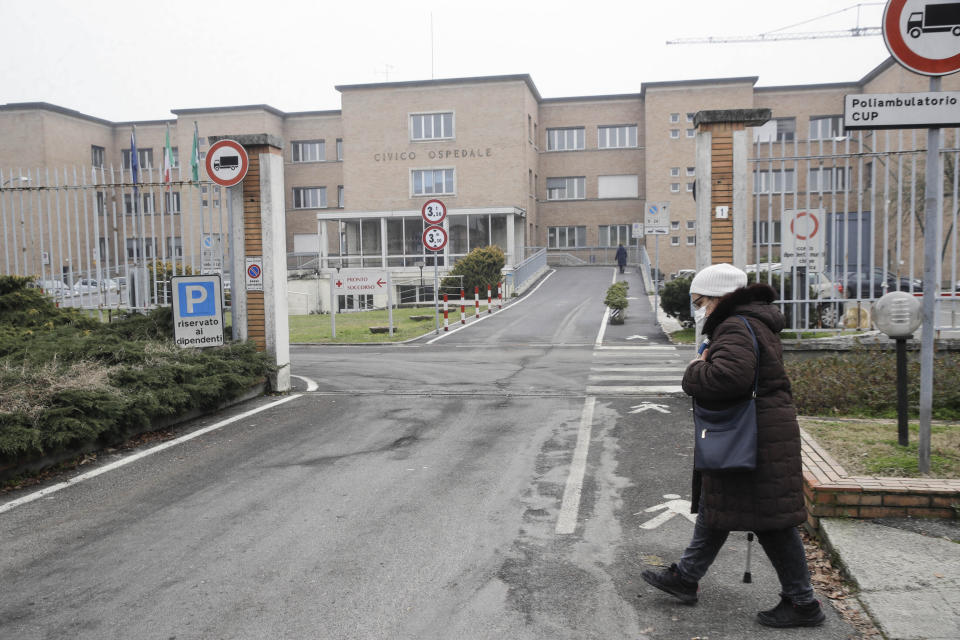 A woman walks in front of the Civic Hospital in Codogno, northern Italy, Sunday, Feb. 21, 2021. The first case of locally spread COVID-19 in Europe was found in the small town of Codogno, Italy one year ago on February 21st, 2020. The next day the area became a red zone, locked down and cutoff from the rest of Italy with soldiers standing at roadblocks keeping anyone from entering of leaving. (AP Photo/Luca Bruno)