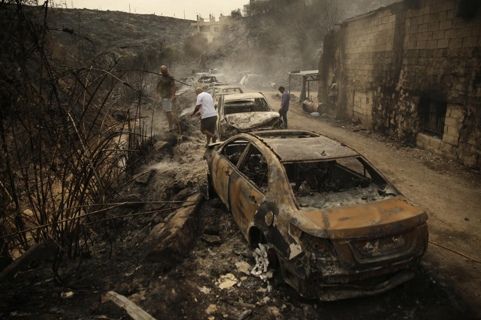 People inspect the remains of cars and shops that were burned in a wildfire overnight, in the town of Damour just over 15km (9 miles) south of Beirut, Lebanon, Tuesday, Oct. 15, 2019. Strong fires spread in different parts of Lebanon forcing some residents to flee their homes in the middle of the night as the flames reached residential areas in villages south of Beirut. (AP Photo/Hassan Ammar)