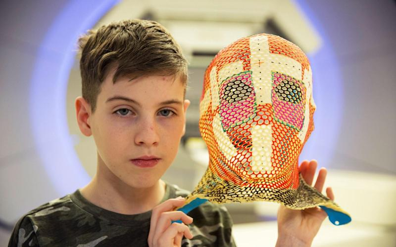 15-year-old Mason holds the mask he wore for his Proton Therapy - BBC