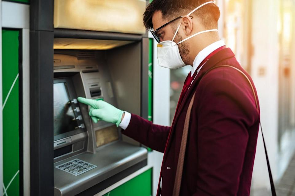 Elegant young man with protective mask standing on city street and using ATM machin with protective gloves on hands. Virus pandemic prevention and healthcare concept.
