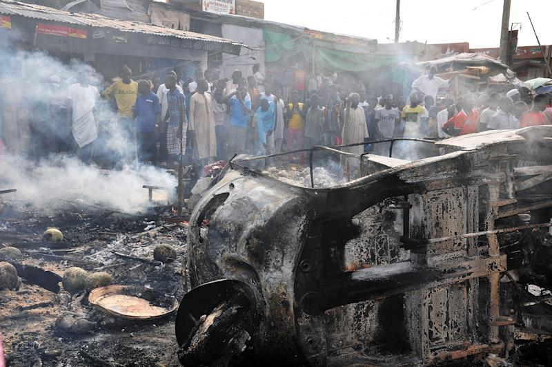 People gather to look at a burnt vehicle following a bomb explosion that rocked the busiest roundabout near the crowded Monday Market in Maiduguri, Borno State, on July 1, 2014 (AFP Photo/)