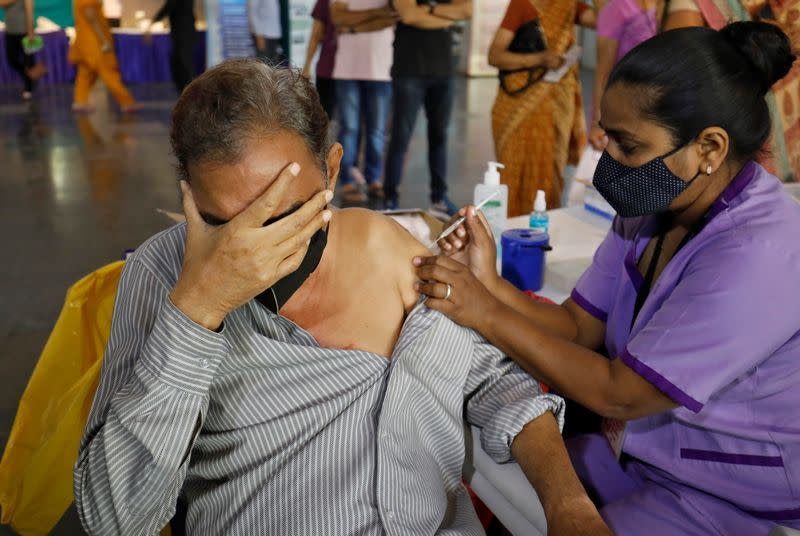 A man reacts as he receives a dose of the COVISHIELD coronavirus disease (COVID-19) vaccine, in Ahmedabad