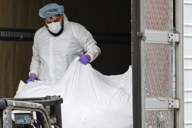 A body wrapped in plastic is loaded onto a refrigerated container truck used as a temporary morgue by medical workers wearing personal protective equipment due to COVID-19 concerns, Tuesday, March 31, 2020, at Brooklyn Hospital Center in the Brooklyn borough of New York. The new coronavirus causes mild or moderate symptoms for most people, but for some, especially older adults and people with existing health problems, it can cause more severe illness or death. (AP Photo/John Minchillo)