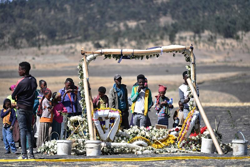 Children from surrounding homesteads stand in front of a flower memorial held for victims at the crash site of an Ethiopian airways operated by a Boeing 737 MAX aircraft on March 16, 2019 at Hama Quntushele village near Bishoftu in Oromia region. The second crash involving the 737 MAX series has spurred reaction among international airline operators to ground Boeing 737 Max aircraft in their fleets.