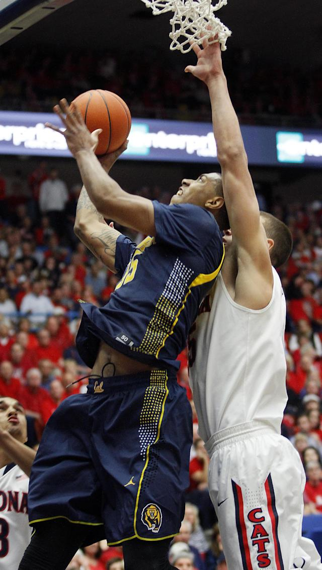 California's Richard Solomon, left, shoots under the basket despite the pressing defense of Arizona's Kaleb Tarczewski, right, in the first half of an NCAA college basketball game on Wednesday, Feb. 26, 2014, in Tucson, Ariz. (AP Photo/John MIller)