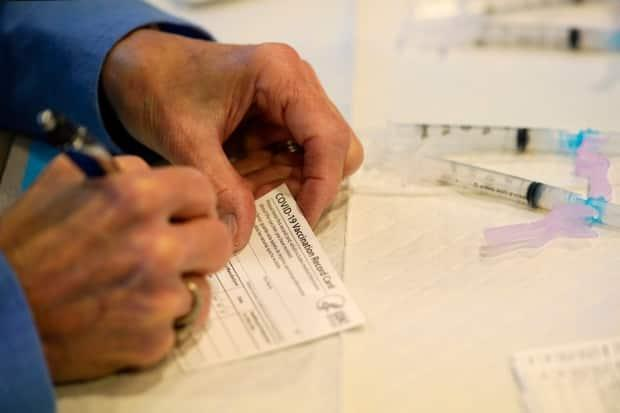 A health department worker in Pennsylvania fills out a vaccination record card before administering the Moderna COVID-19 vaccine to emergency medical workers and health-care personnel on Dec. 29, 2020. Nova Scotia's proof-of-vaccination policy comes into effect Monday, Oct. 4. (Matt Slocum/The Associated Press - image credit)