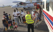 People fleeing fighting between insurgents and government forces in and around the northern Mozambican town of Palma arrive after being evacuated by plane to the Cabo Delgado provincial capital of Pemba, Mozambique, Thursday April 1, 2021. They were just a few of the thousands of residents who have fled to nearby Tanzania and south to the provincial capital of Pemba, according to international aid agencies. (Dave LePoidevin, MAF via AP)