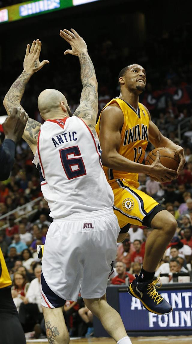 Indiana Pacers forward Evan Turner (12) drives to the basket as Atlanta Hawks center Pero Antic (6) defends in the first half of Game 4 of an NBA basketball first-round playoff series, Saturday, April 26, 2014, in Atlanta. (AP Photo/John Bazemore)