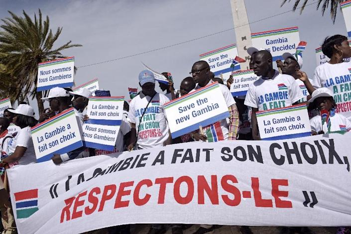 """People hold a banner reading """"Gambia made its choice, let's respect it"""" during a protest in support of Gambia by Senegalese NGOs and civil rights groups in Dakar (AFP Photo/SEYLLOU)"""
