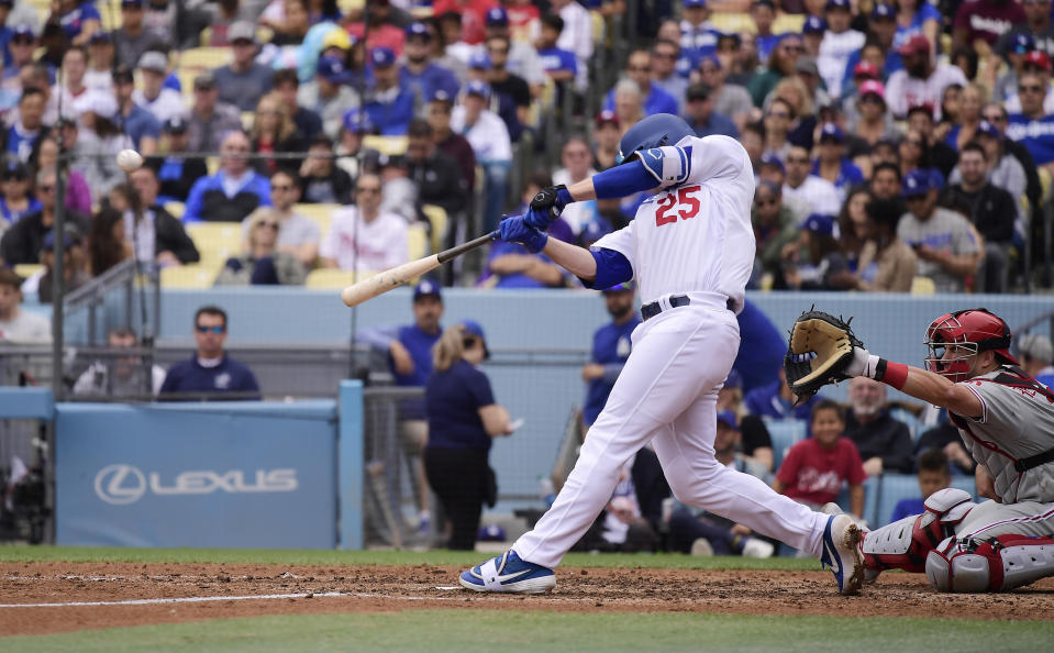 Los Angeles Dodgers' David Freese (25) hits a solo home run as Philadelphia Phillies catcher J.T. Realmuto watches during the seventh inning of a baseball game Sunday, June 2, 2019, in Los Angeles. (AP Photo/Mark J. Terrill)