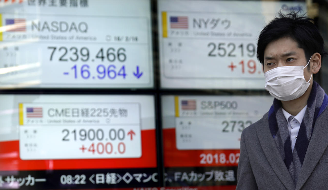 A man walks past an electronic stock indicator of a securities firm in Tokyo, Tuesday, Feb. 20, 2018. Asian shares were mostly lower Tuesday after a U.S. holiday and attention turned to the U.S. Federal Reserve. (AP Photo/Shizuo Kambayashi)