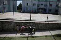 Luana Vieira, who is two years old, and was born with microcephaly, is pushed in a wheelchair by her sister Vitoria Evillen, near a sports court in the housing complex where they live, in Olinda, Brazil, August 6, 2018. REUTERS/Ueslei Marcelino/Files